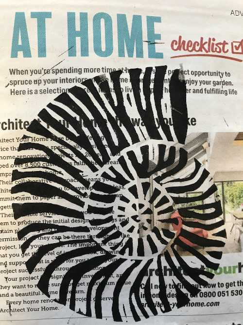 Linocut print of shell superimposed on a newspaper advert