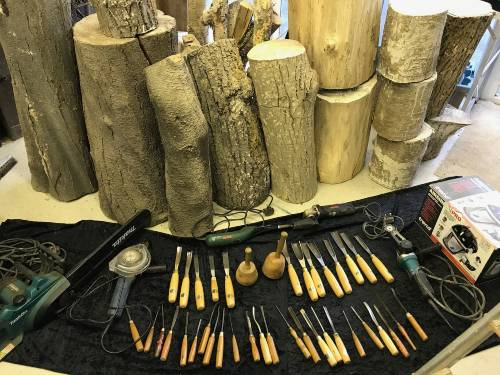 Wood carving tools in front of logs for sculpture project