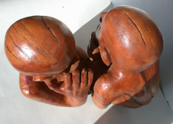 Cherry wood sculpture of people whispering to each other by Peter Heywood