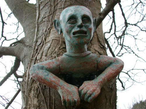 Ceramic sculpture of a spooky man stuck in a tree, by Peter Heywood